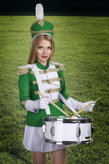 cheerleader  with drum on the background of green grass