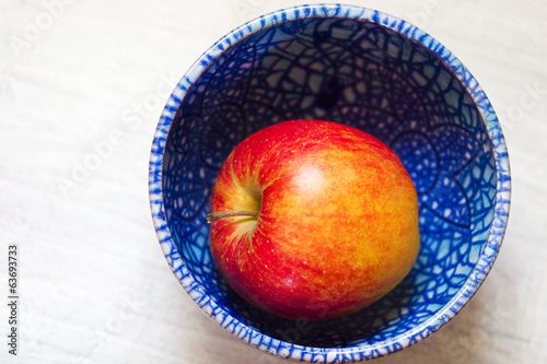 red ripe juicy apple on a beautiful plate