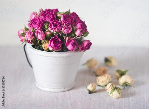 bouquet of pink roses in a decorative small white bucket