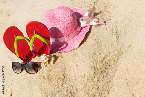 Red flip flop with sunglasses and pink floppy hat on beach