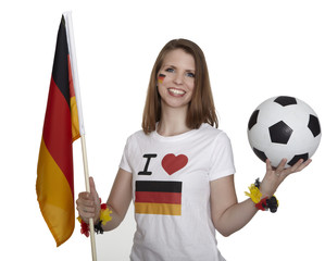 Attractive woman shows german flag and football and smiles