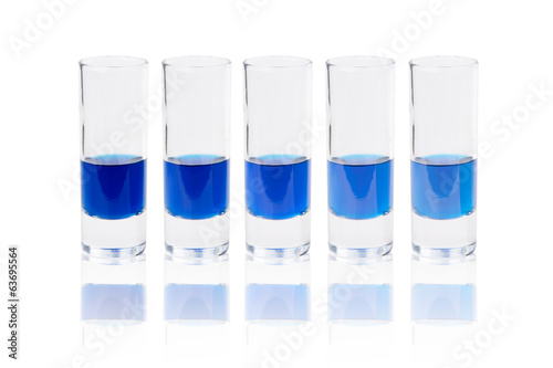 Six glasses with blue liquid