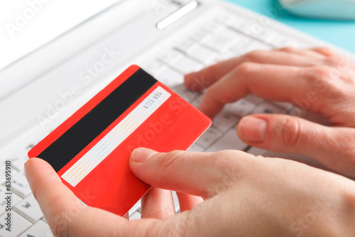 Woman holding a credit card for online shopping.