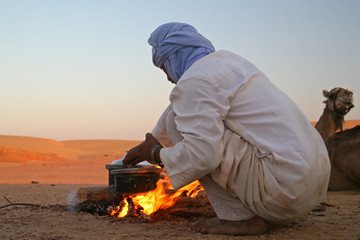 Native arab bedouin making a dinner in the desert