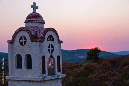Small church or chapel with typical Greek landscape at sunset