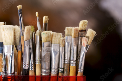 Artist's brushes in front of a colorful background