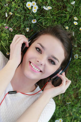 Portrait de femme allongée dans l'herbe écoutant de la musique