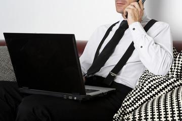 Mann sitzt am Computer und telefoniert