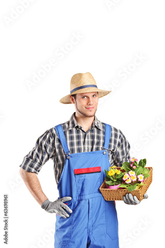 Male gardener holding a basket with flowers