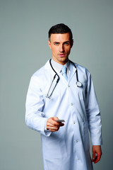 Confident male doctor giving card on gray background