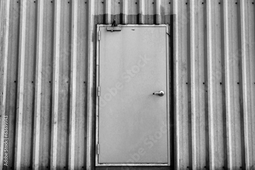 iron door on corrugated metal sheet, black and white photo