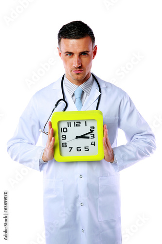 Confident male doctor holding clock isolated on white background