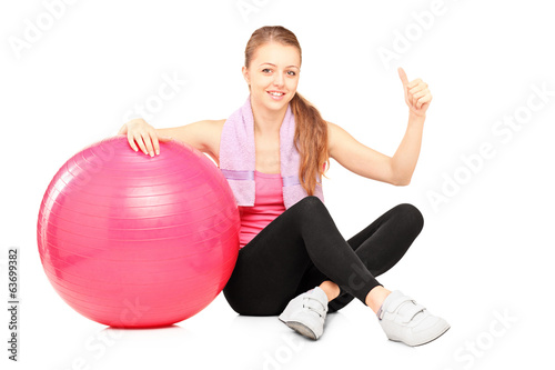 Woman sitting by pilates ball and giving thumb up