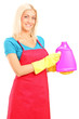Young woman holding a bottle of cleaning solution
