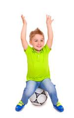 Happy little boy sitting on  soccer ball
