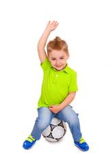 Little boy sitting on  soccer ball