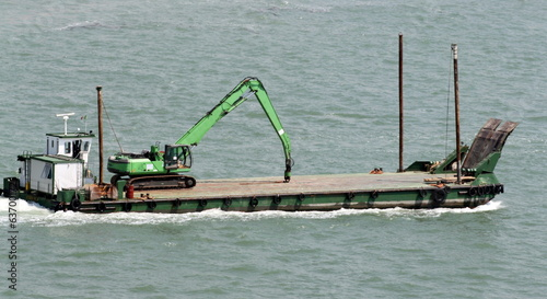 transport boat with a heavy bulldozer over heads to the shipyard