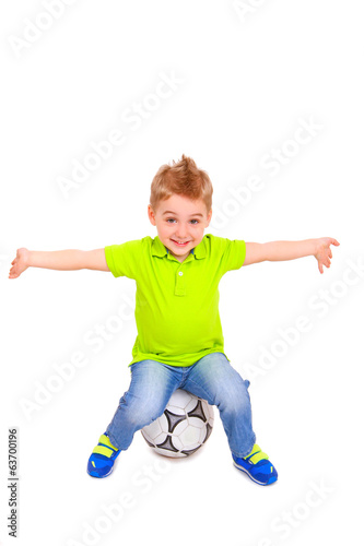 Happy little boy sitting on a soccer ball