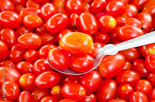 Cherry tomato in on spoon over tomatos background