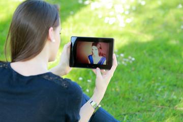 Jeune femme regardant sa photo sur sa tablette