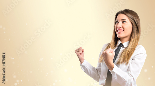 Young businesswoman winning over ocher background
