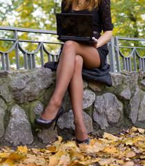 Young teen girl using laptop - autumn