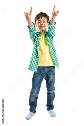 Kid doing the horn sign over white background