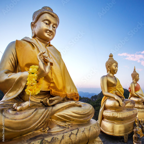 Golden Buddha statues on the top of the mountain in Tiger Temple