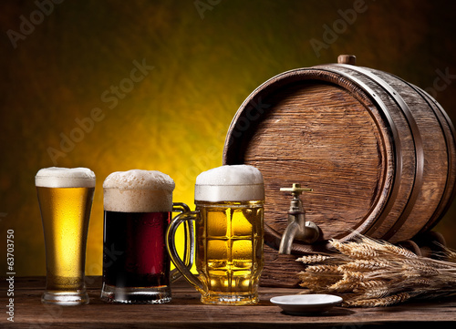Beer glasses, old oak barrel and wheat ears.