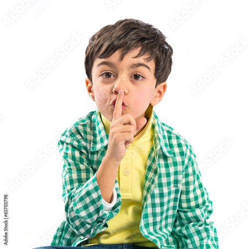 Kid doing silence gesture over white background