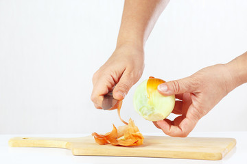 Hands peeling raw onion with a knife on a cutting board
