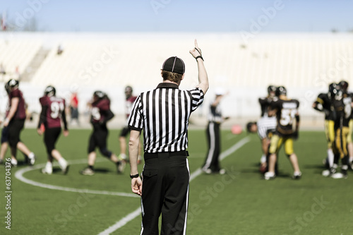 American football referee with hand up