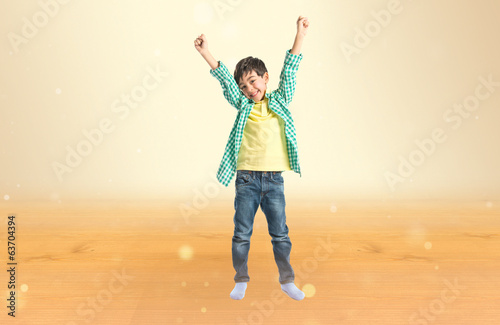 Lucky brunette kid over isolated ocher background