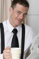 Mann liest Zeitung mit Tasse in der Hand