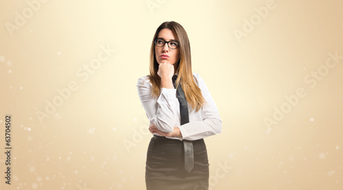 Cute young girl thinking an idea over ocher background