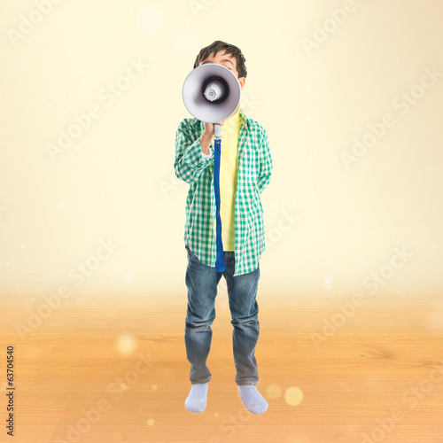Kid shouting by megaphone over ocher background