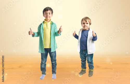 Boys making OK sign over ocher background