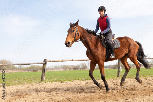 Foto op Canvas Paardensport Young woman riding a horse