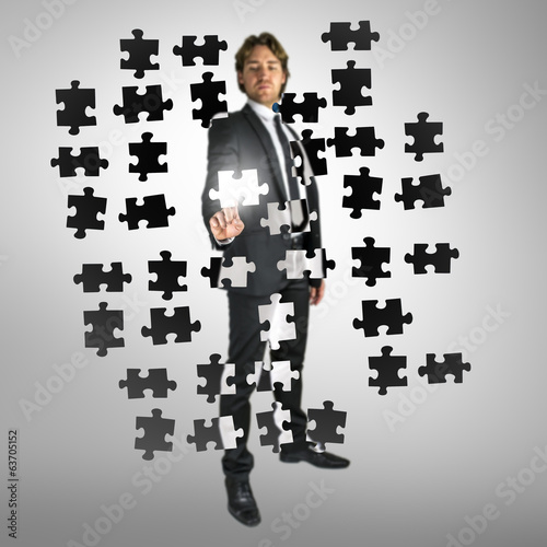 Businessman selecting a puzzle piece