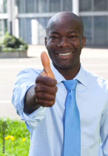 African businessman in front of his office showing thumb