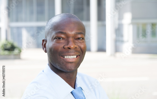 Laughing african businessman in front of his office