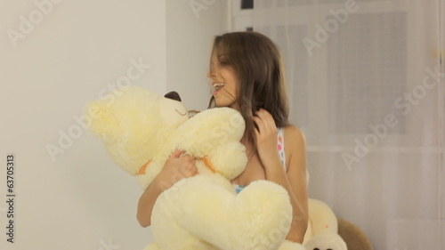 Girl dancing on the bed with a toy