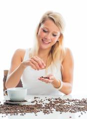 Blonde Frau mit Kaffeetasse und Bohnen