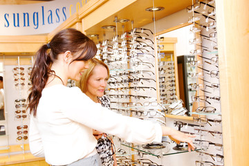 Optician assisting customer with options for glasses