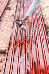 Worker painting steel bar.