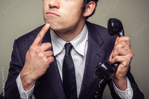Businessman on the phone is thinking