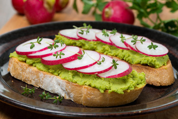 toasted ciabatta with pate of avocado and fresh radish, close-up