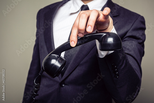 Businessman holding phone with his fingers