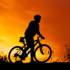 silhouette of bicycle rider at sunset