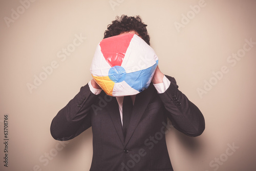 Businessman blowing up a beach ball